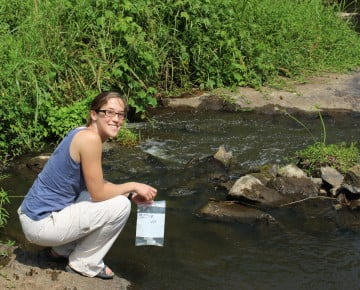 Marian Hamilton collecting water and plant samples from the Mpanga River in the northern section of Kibale National Park
