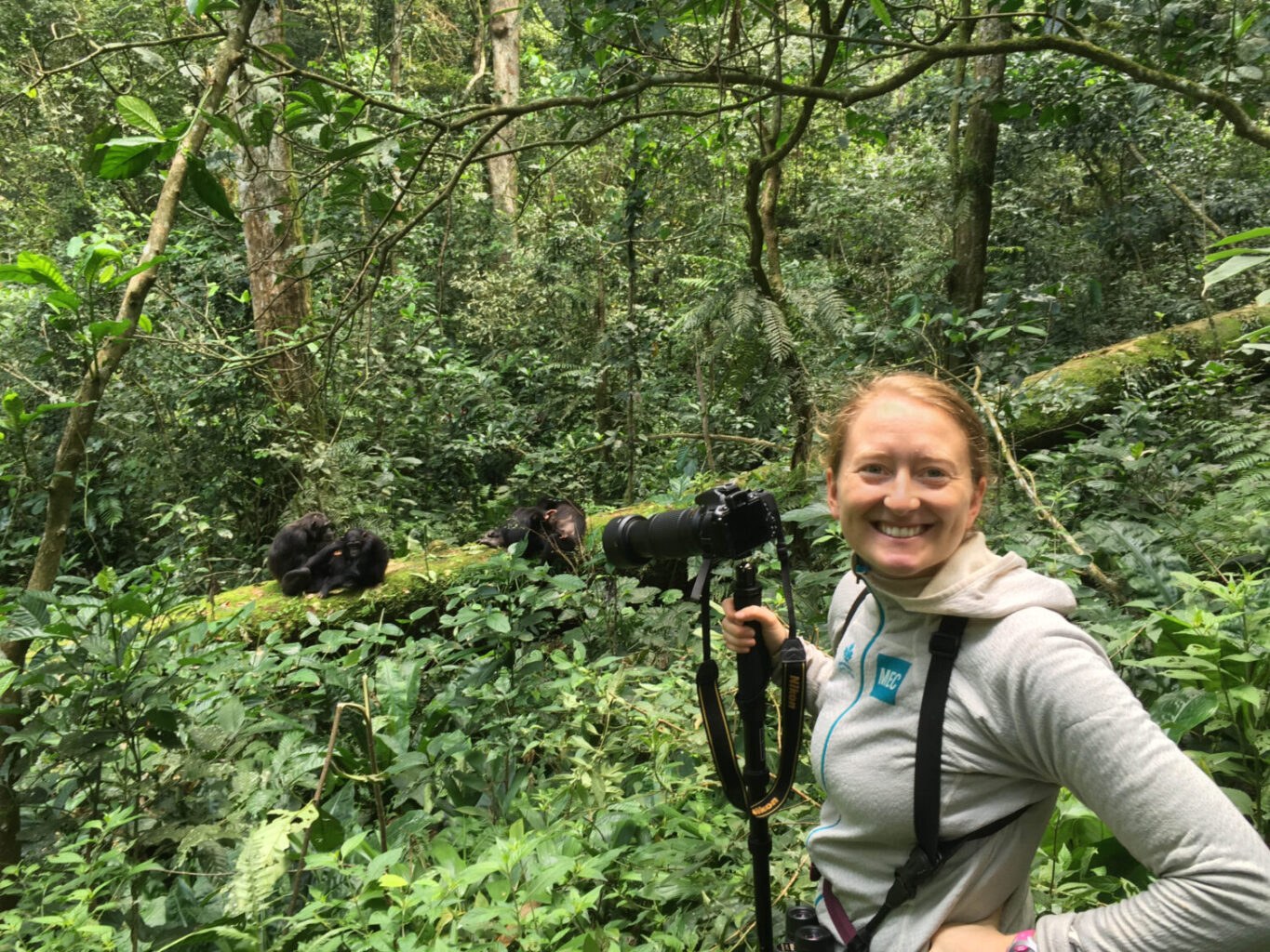 A smiling scientist is in a green leafy forest. She is holding a camera and looking at the viewer. Several chimpanzees are behind her, grooming each other on a moss-covered log.