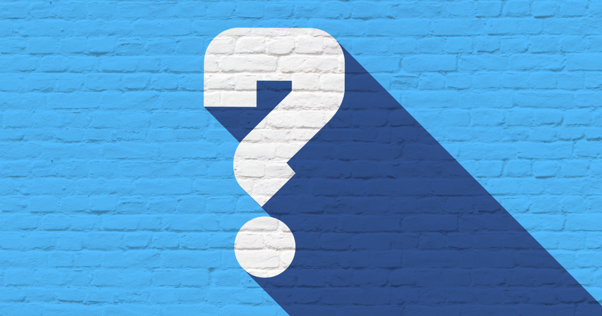 A blue painted brick wall with a large white question mark